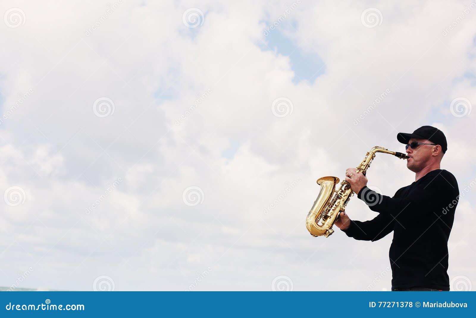 Саксофонист играя на саксофоне внешнем