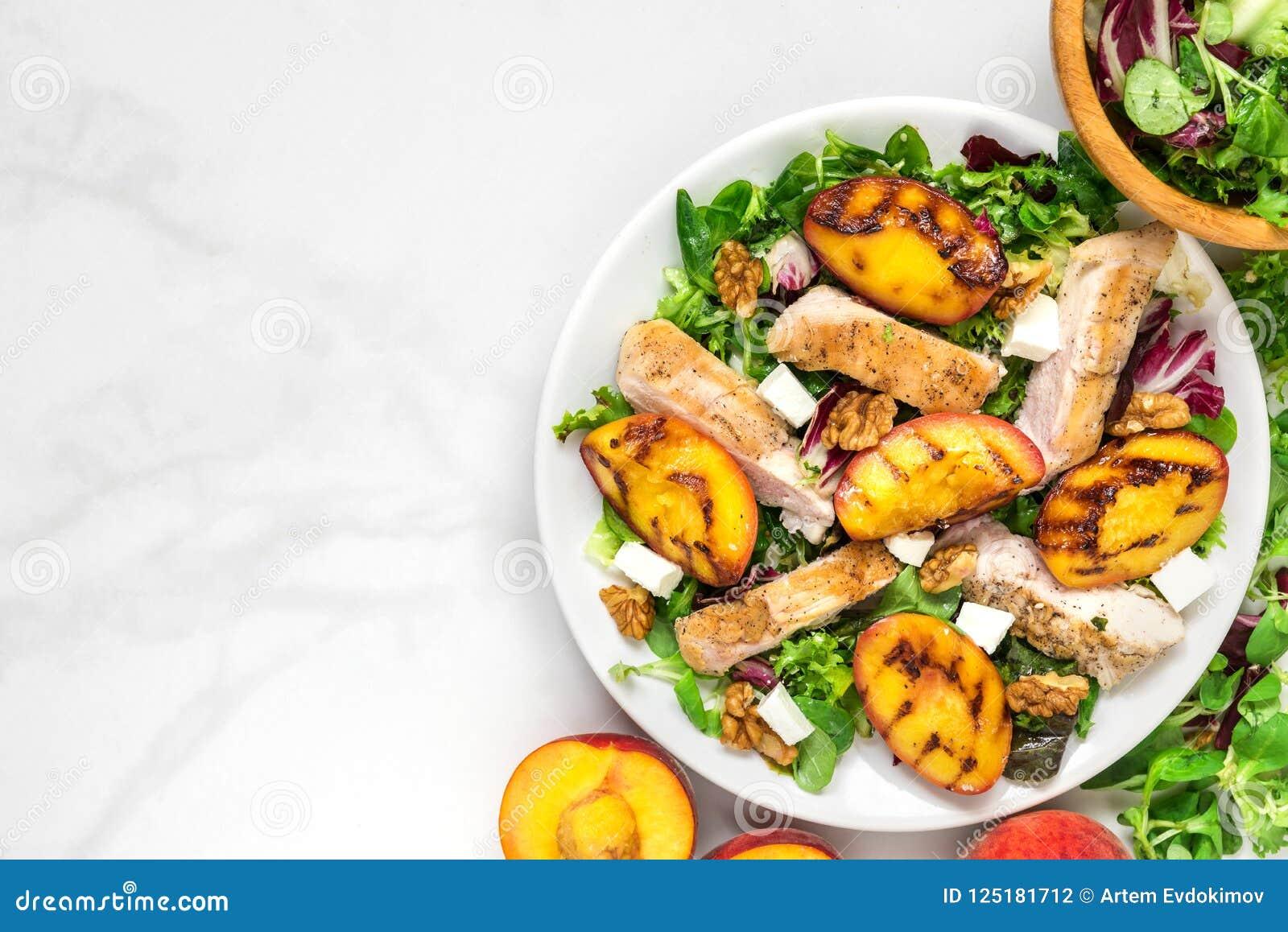 Салат витамина с зажаренными цыпленком и персиком, сыром фета и грецкими орехами в плите еда здоровая Взгляд сверху
