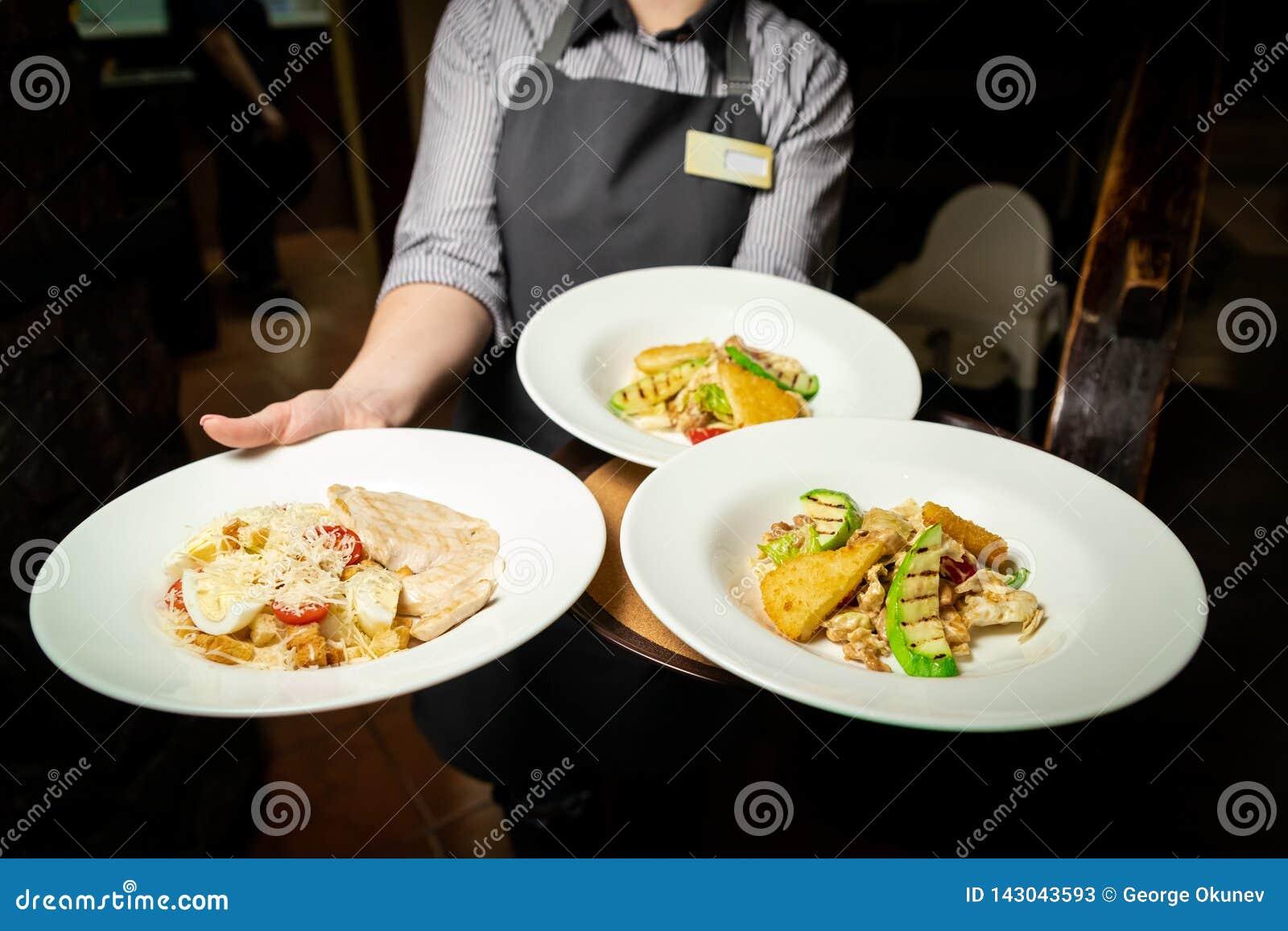 Салат овощей и мяса на красивой белой плите