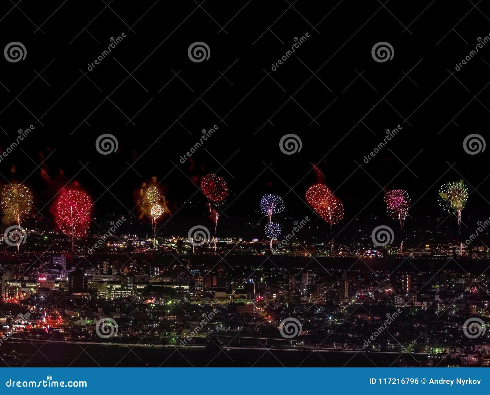 Салют над городом мегаполис Праздничный салют в ночном небе Взрывы фейерверков