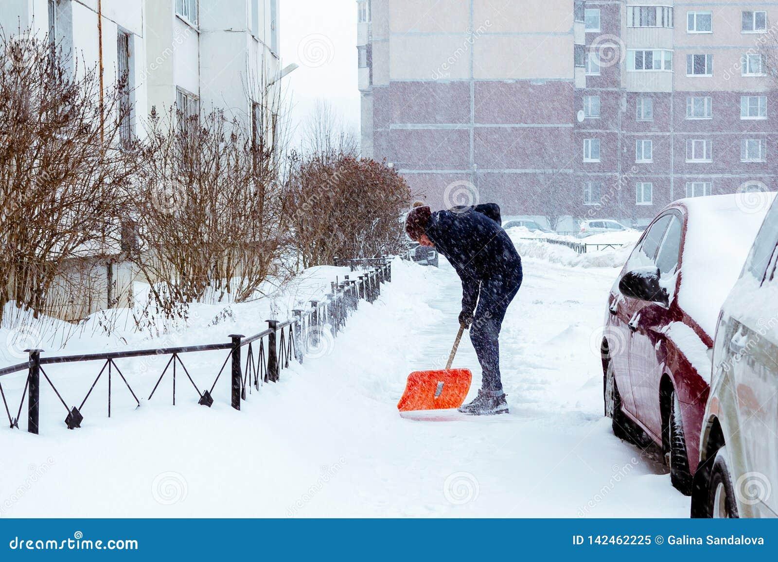 Санкт-Петербург, Россия - 17-ое января 2019: Человек очищает снег во дворе с лопаткоулавливателем после сильного снегопада