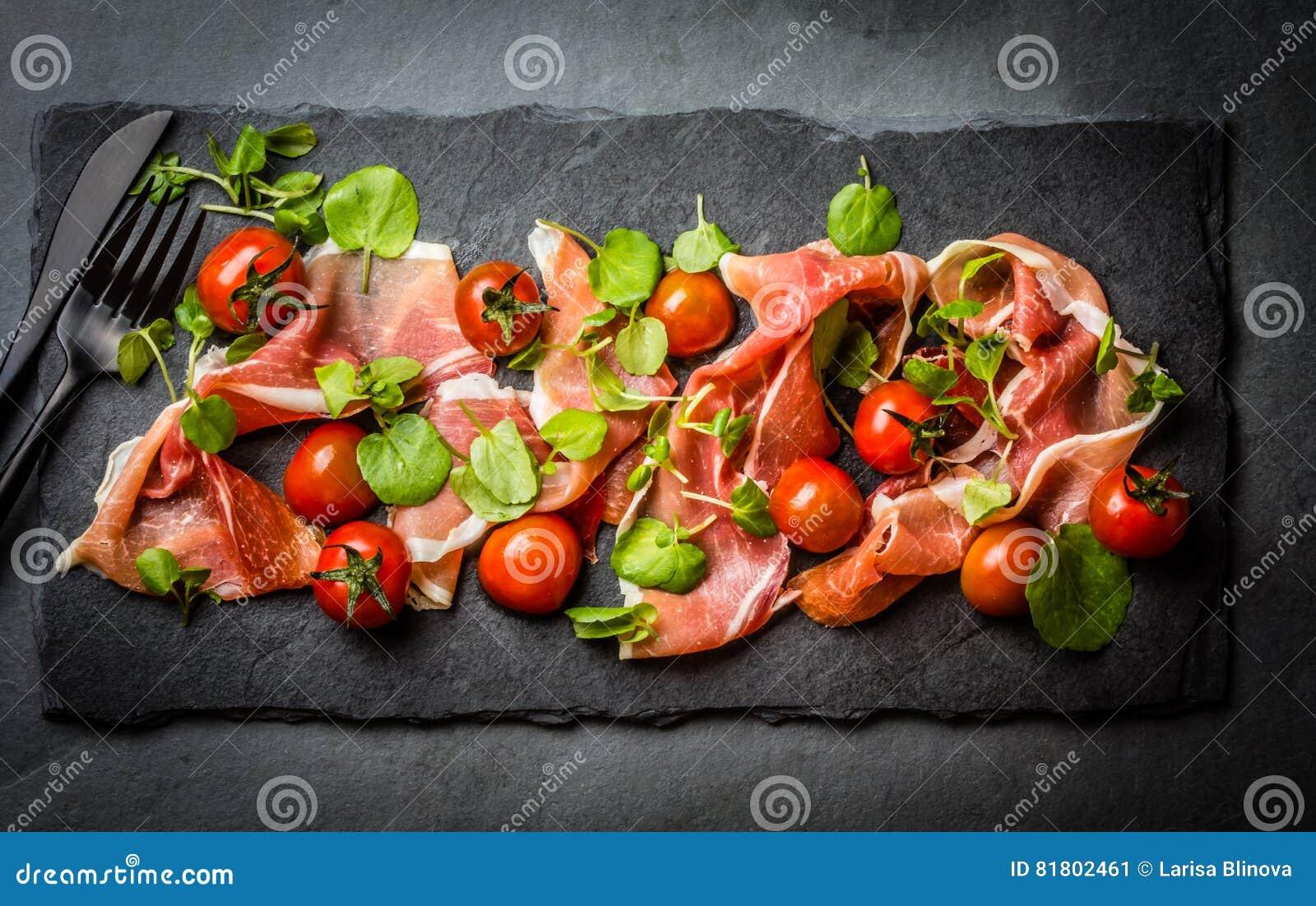 Салат с serrano jamon ветчины, томатами вишни, arugula, доской шифера