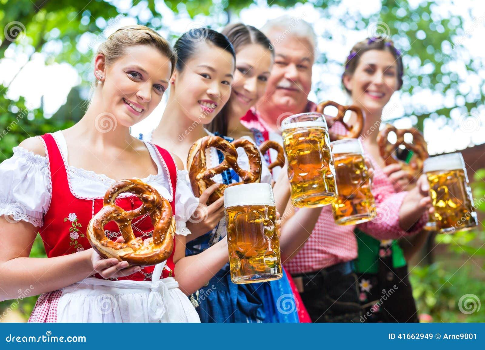Сад пива - друзья выпивая в пабе Баварии