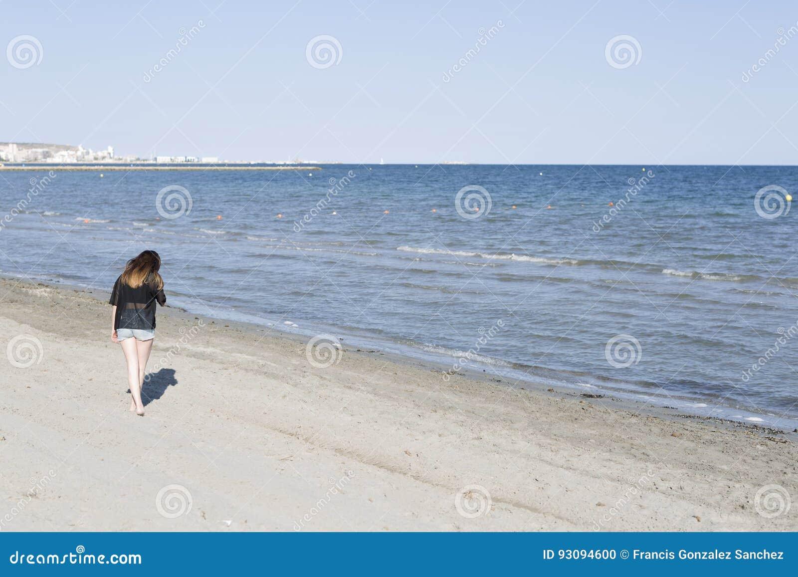 Сбрасывание молодой женщины идя пляжем