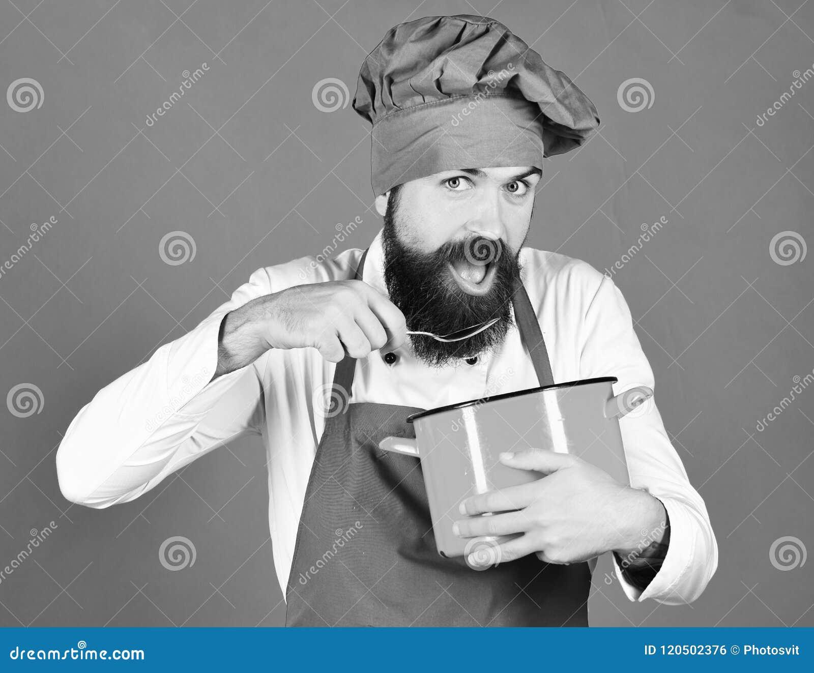 Сварите с голодной стороной в бургундской шляпе и рисберма держит бак и ложку Человек с бородой держит kitchenware на зеленом цве
