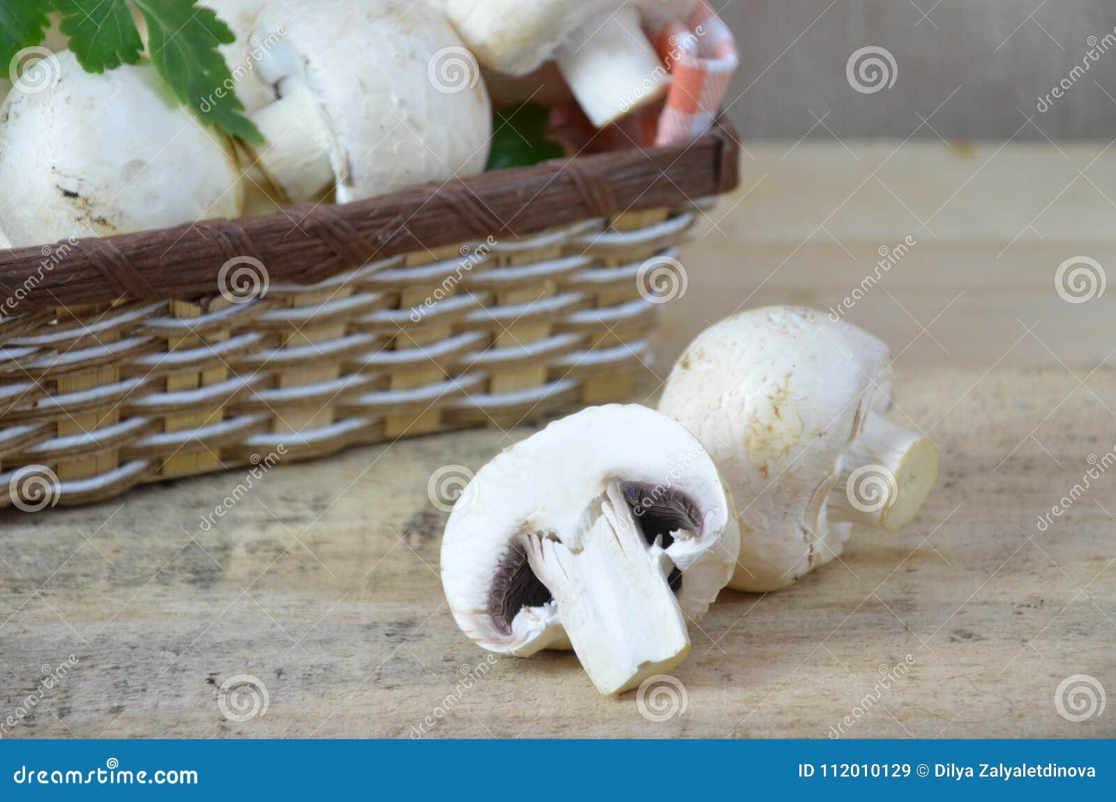 Свежая белизна величает champignon в коричневой корзине на деревянной предпосылке Взгляд сверху скопируйте космос