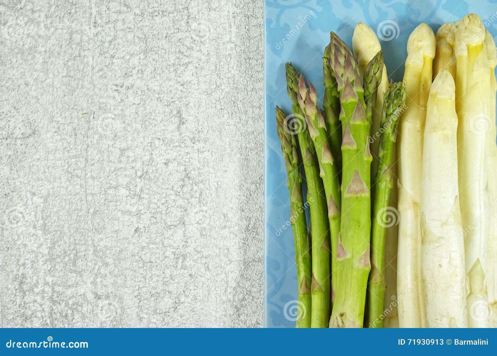 Свежая белая и зеленая спаржа на голубой доске