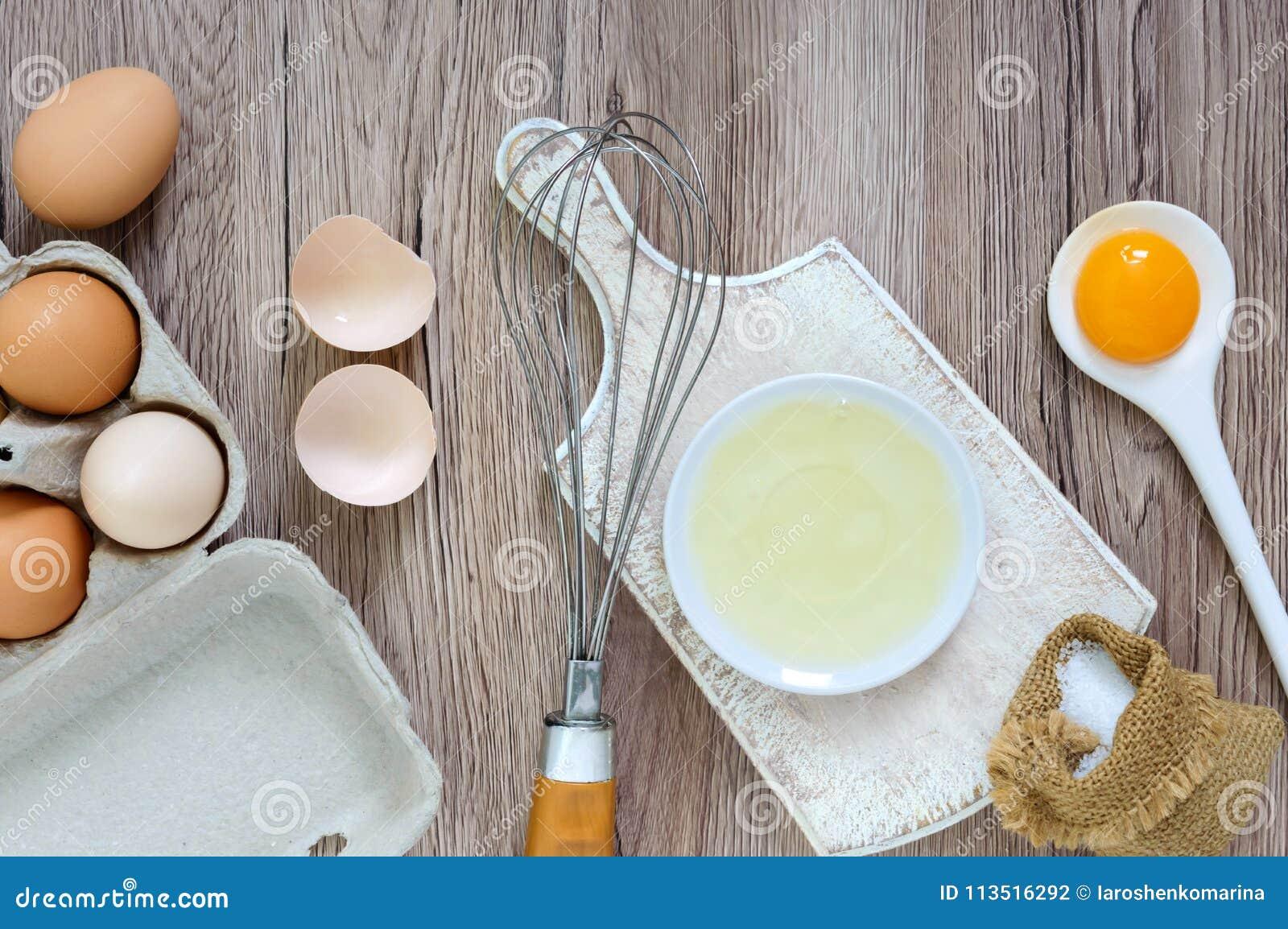 Свежая ферма eggs на деревянной деревенской предпосылке Отделенная белизна яичка и желтки, сломанные раковины яичка