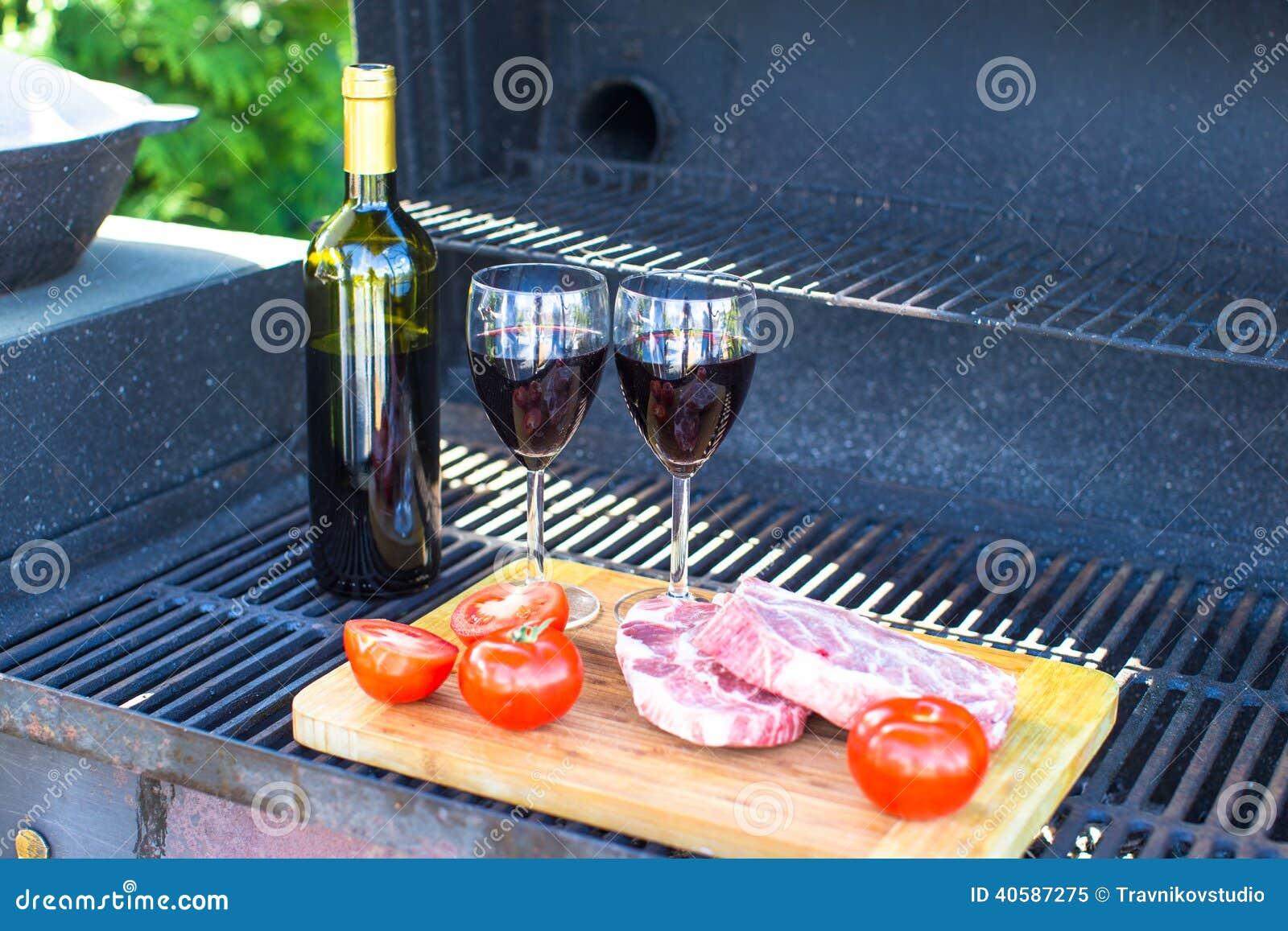 Свежее мясо, овощи и бутылка вина на пикнике outdoors
