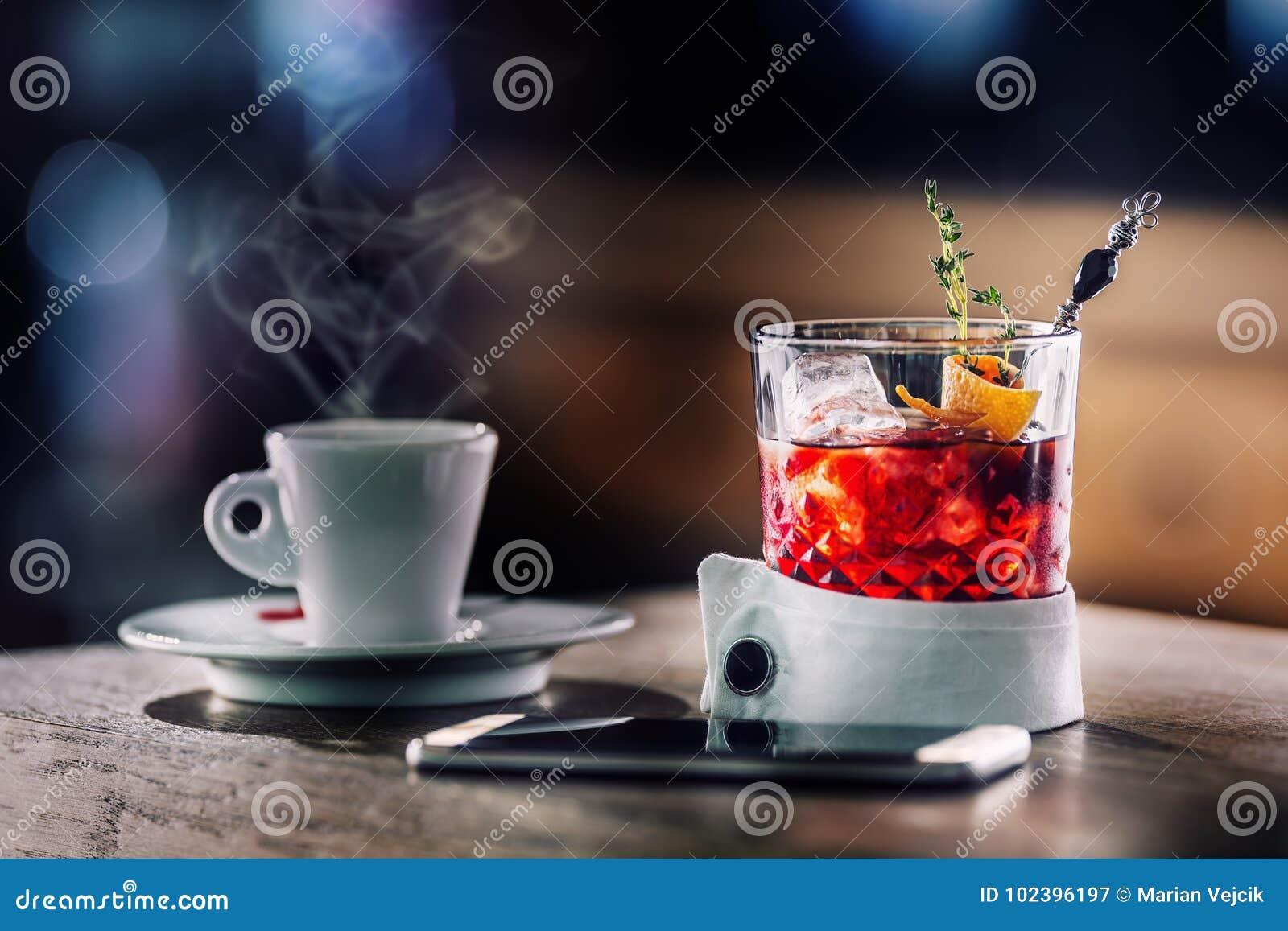Свежее питье коктеиля с чашкой кофе и smartphone Алкоголичка, безалкогольный пить-напиток на счетчике бара в пабе
