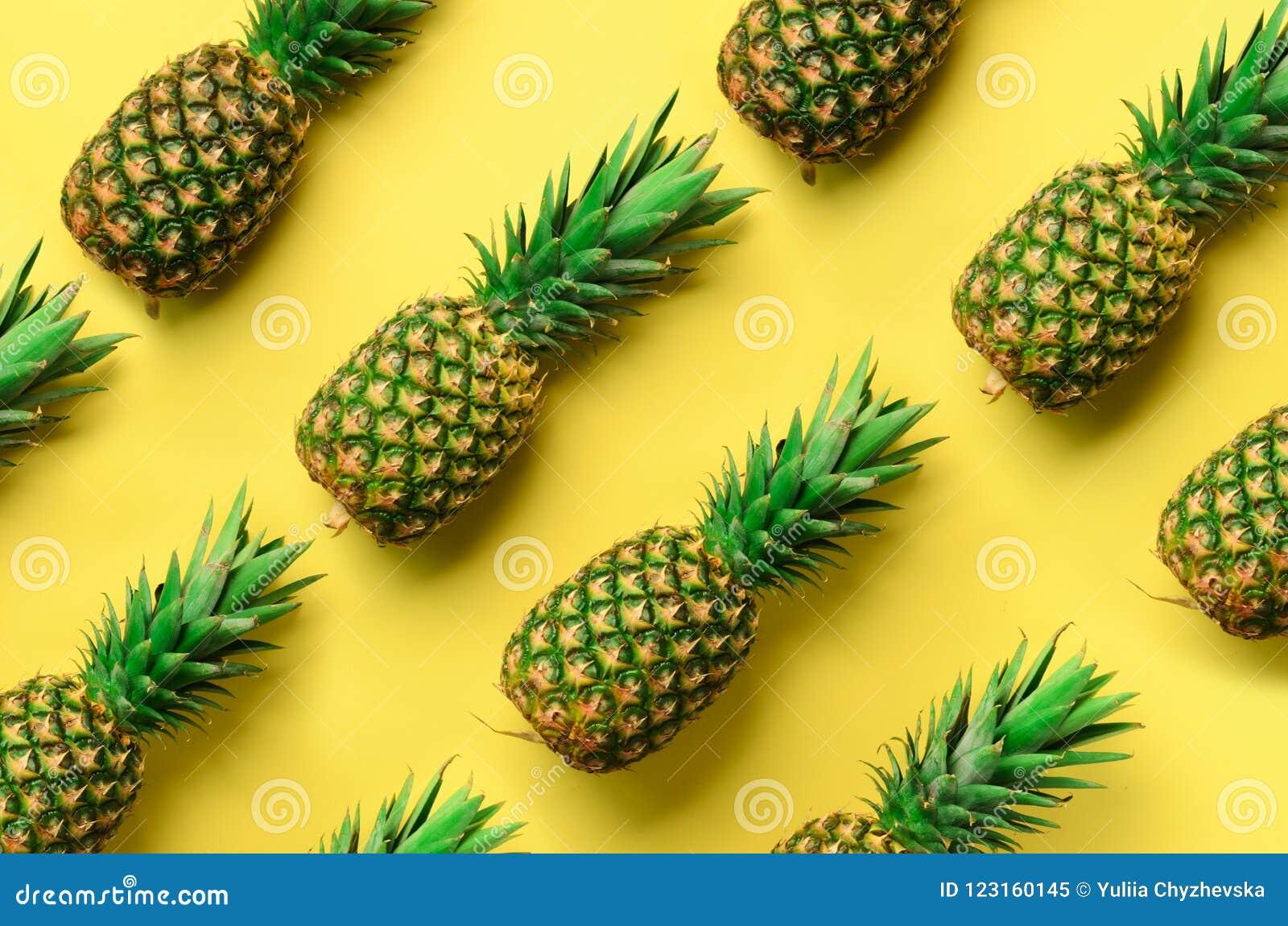 Свежие ананасы на желтой предпосылке Взгляд сверху Дизайн искусства шипучки, творческая концепция скопируйте космос Яркая картина