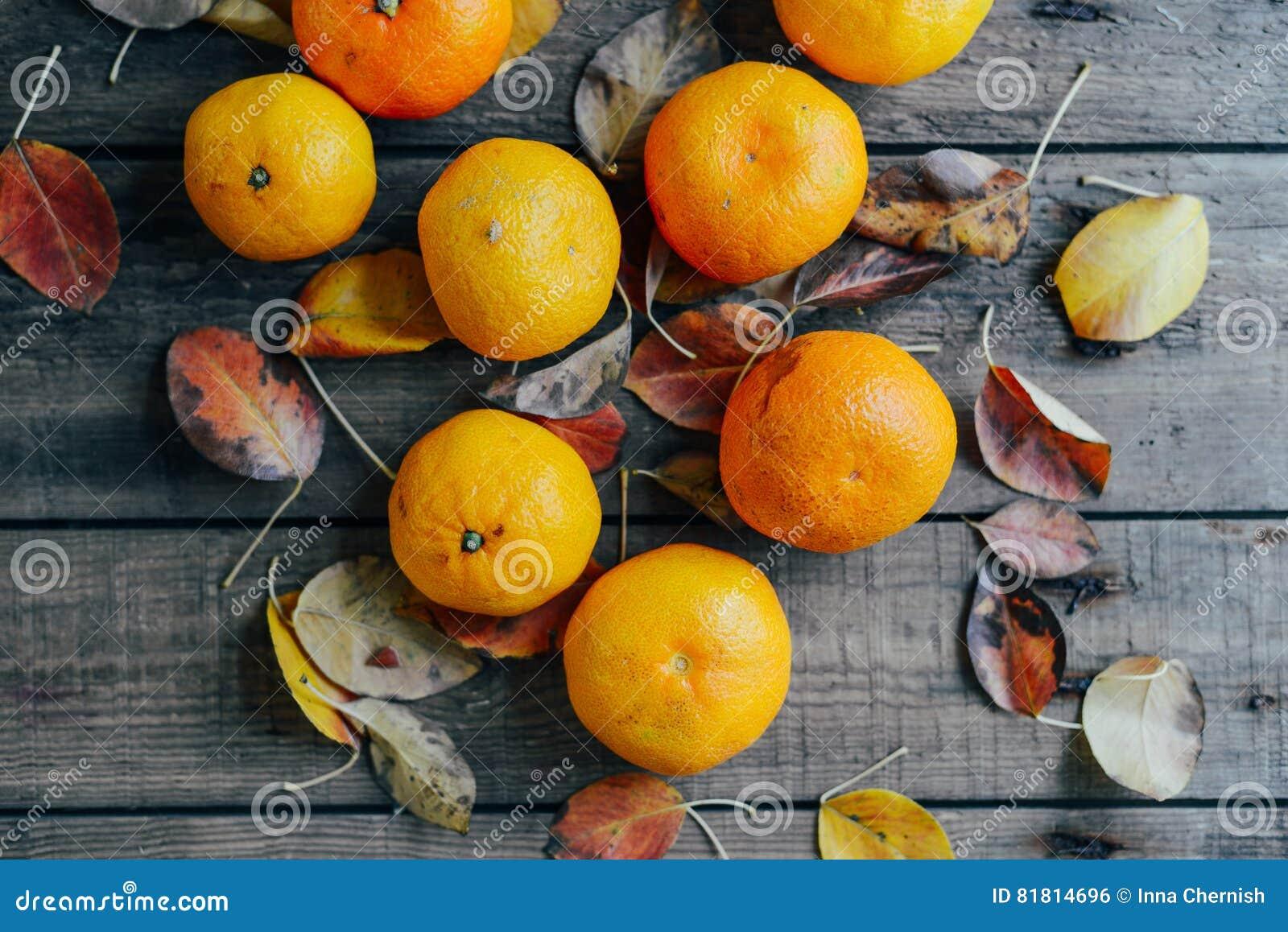 Свежие апельсины мандарина приносить с листьями на деревянном столе зрело