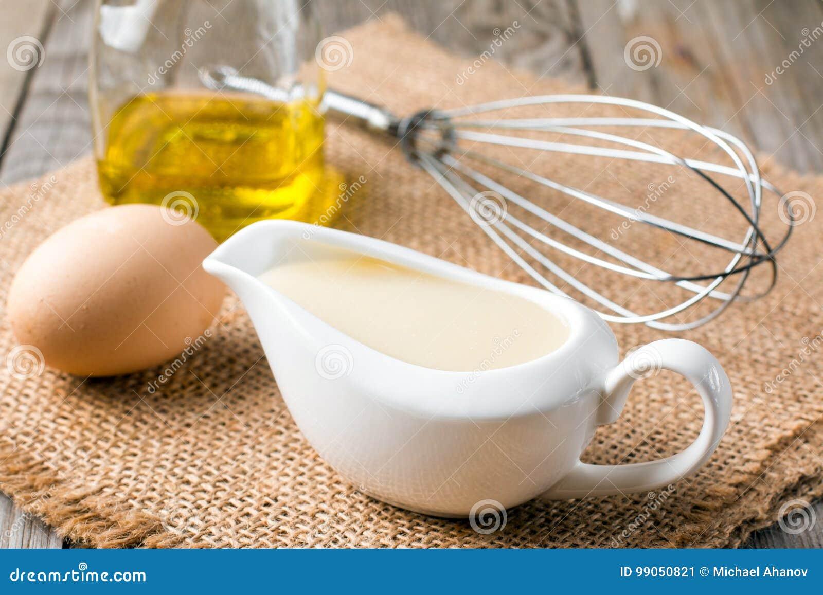 Свежие домодельные майонез белого соуса и яичка ингридиентов, оливковое масло лимона на деревянной предпосылке
