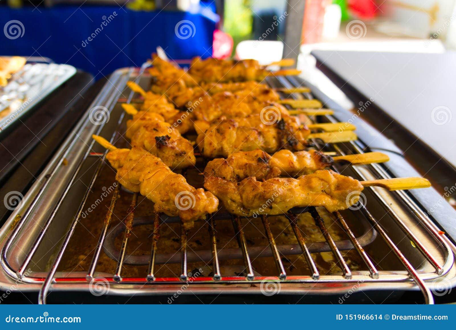 Свежие зажаренные ручки цыпленка satay проданные на ярмарке улицы
