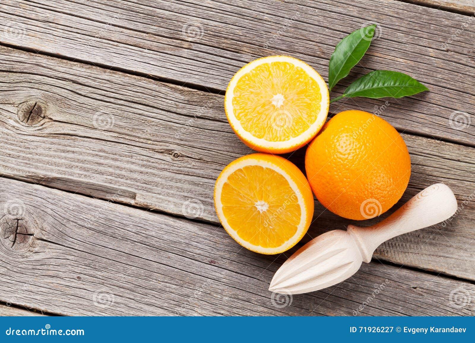 Свежие зрелые апельсины и juicer