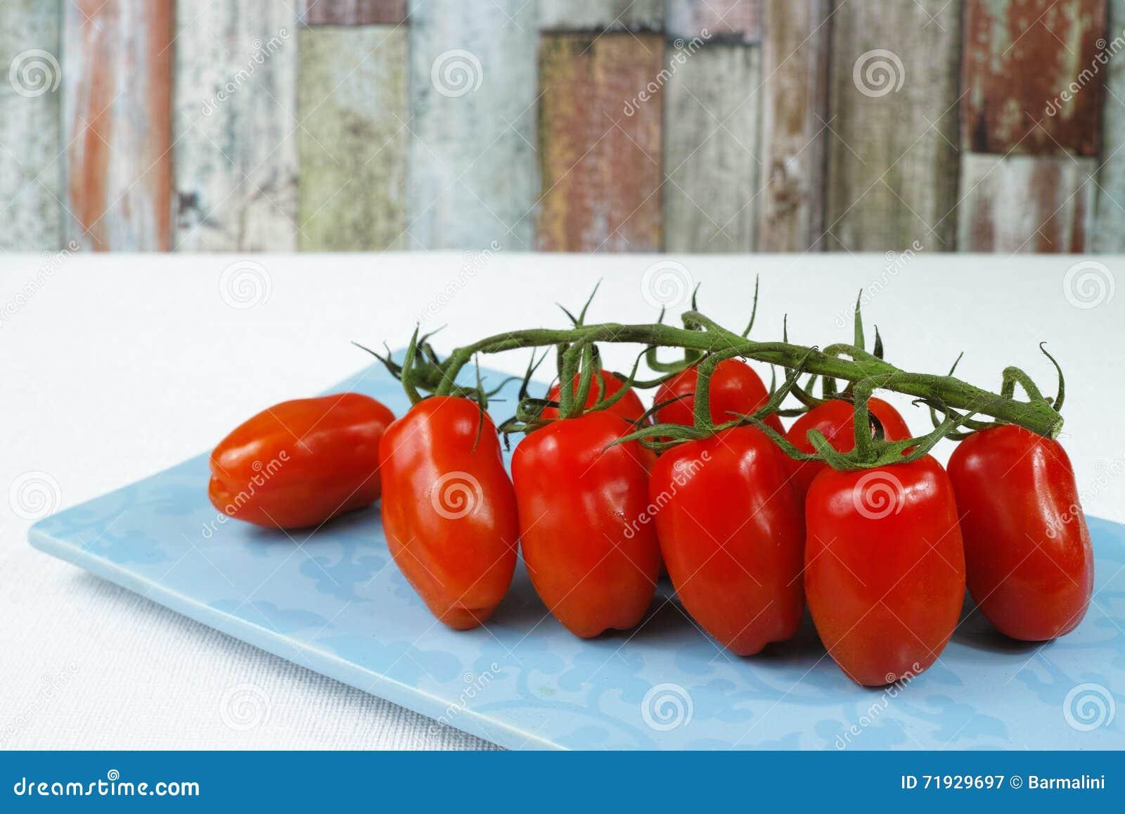 Свежие зрелые мини томаты marzano на голубой доске