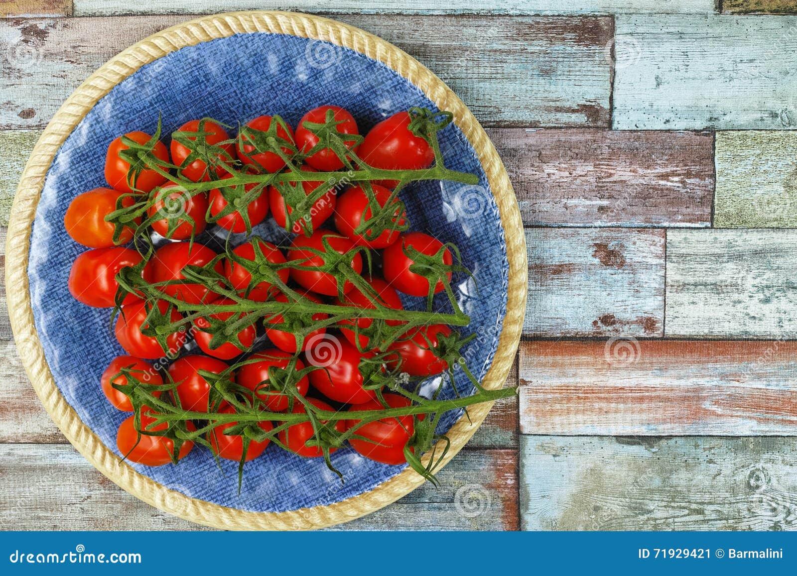 Свежие зрелые мини томаты marzano на голубой плите