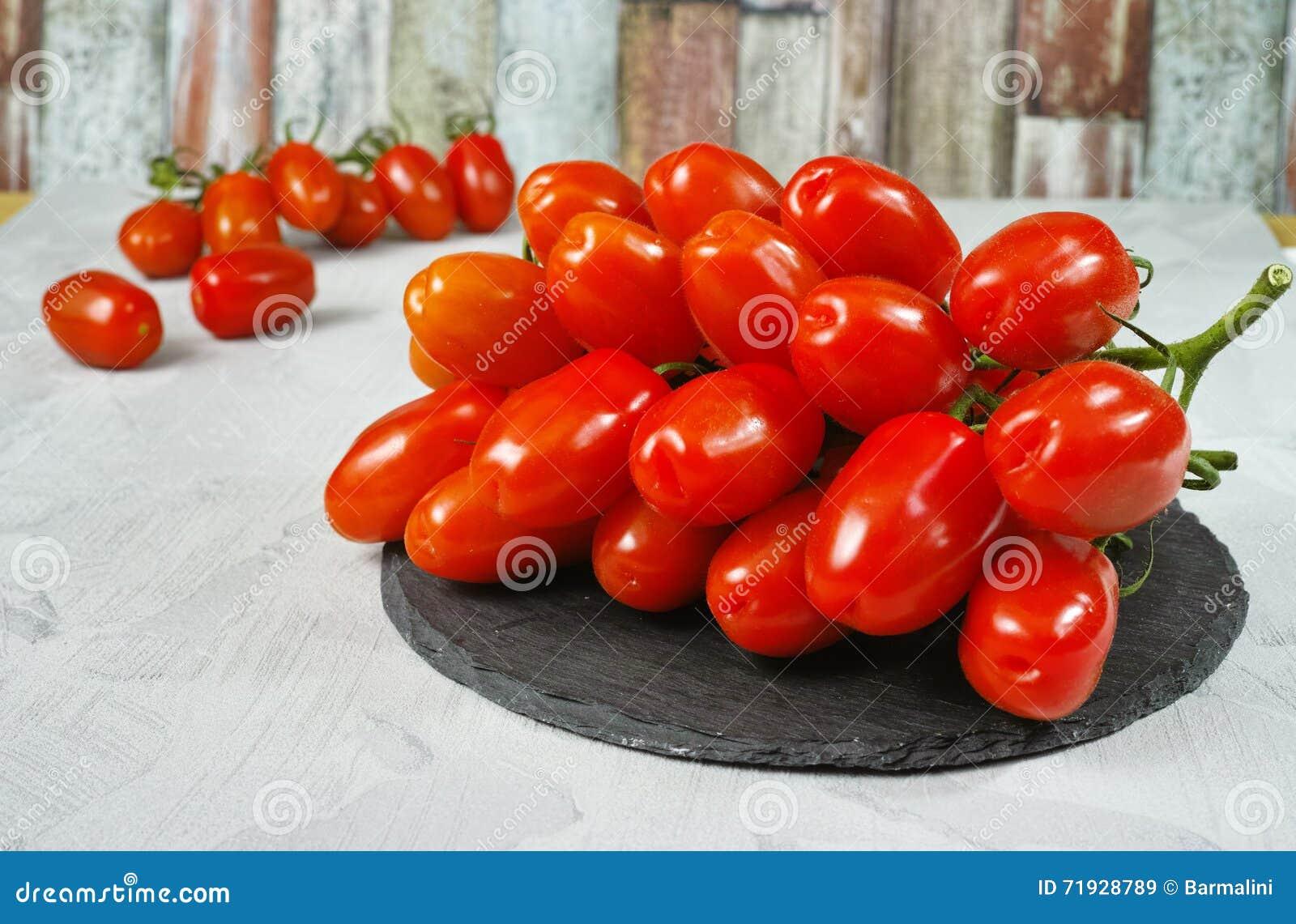 Свежие зрелые мини томаты roma на серой доске