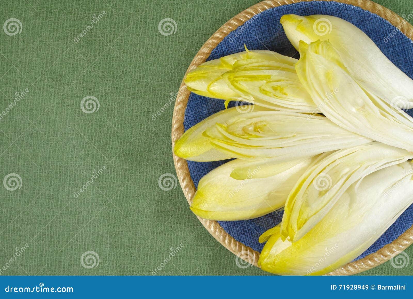 Свежие листья салата цикория помещенные на голубой плите