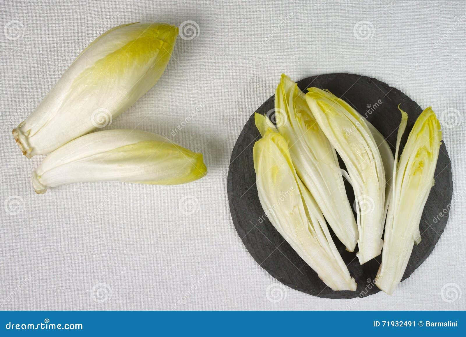 Свежие листья салата цикория помещенные на серой каменной доске