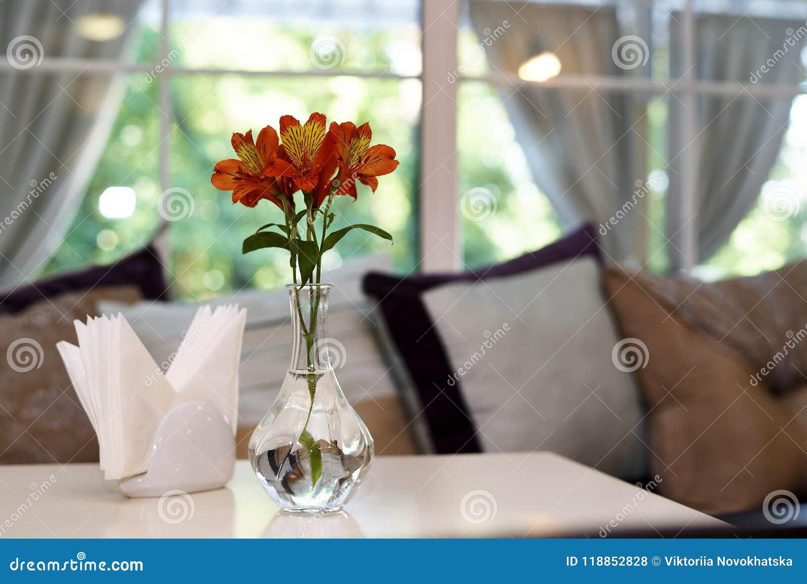 Свежие лилии в стеклянной вазе с водой на таблице