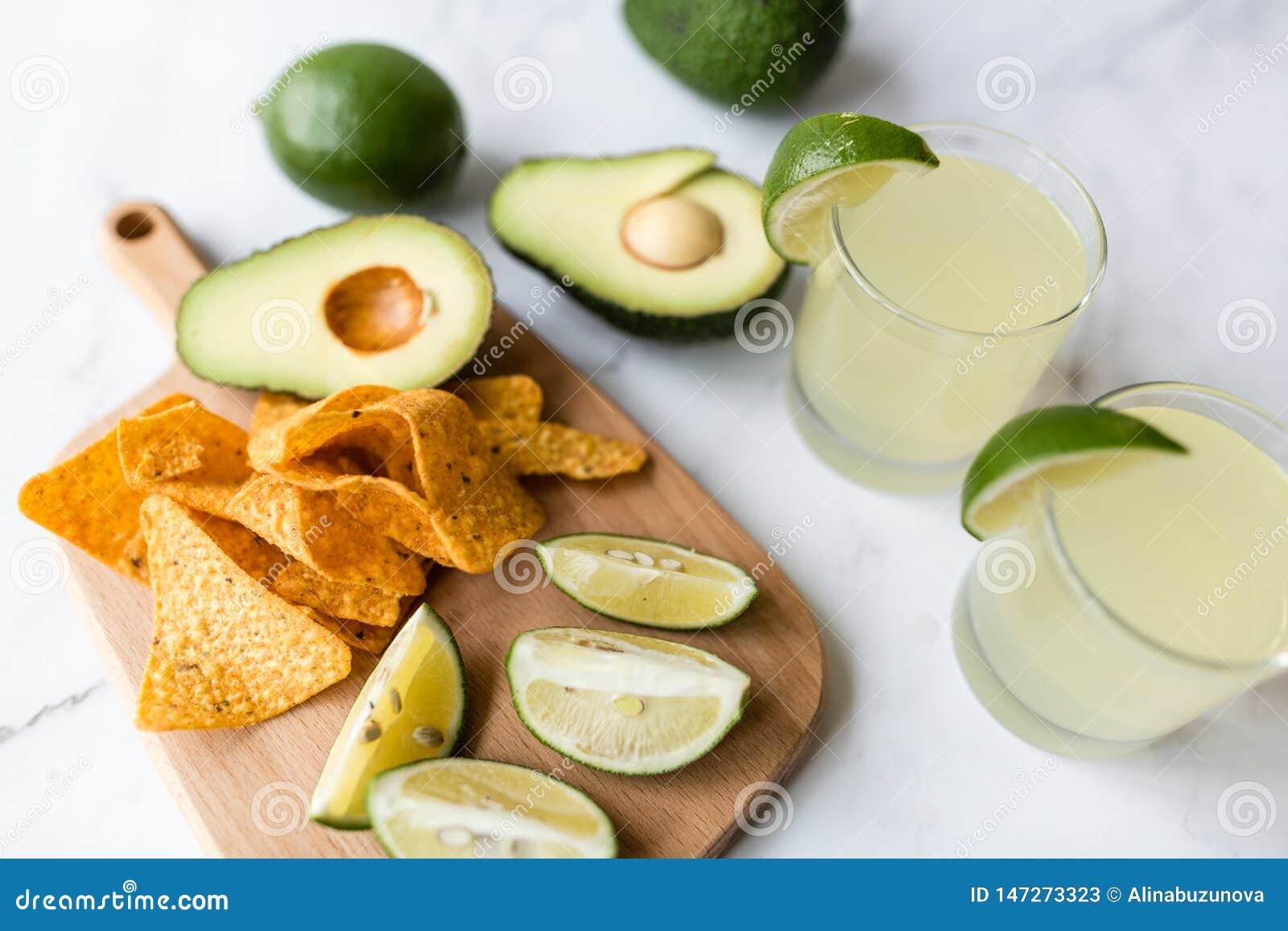 Свежие обломоки авокадоа, известки, напитка и nacho лежа на мраморной предпосылке Рецепт для партии Cinco de Mayo