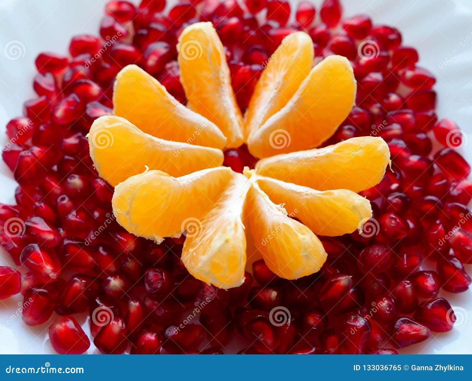 Свежие фрукты на белой плите Куски зерен мандарина и гранатового дерева