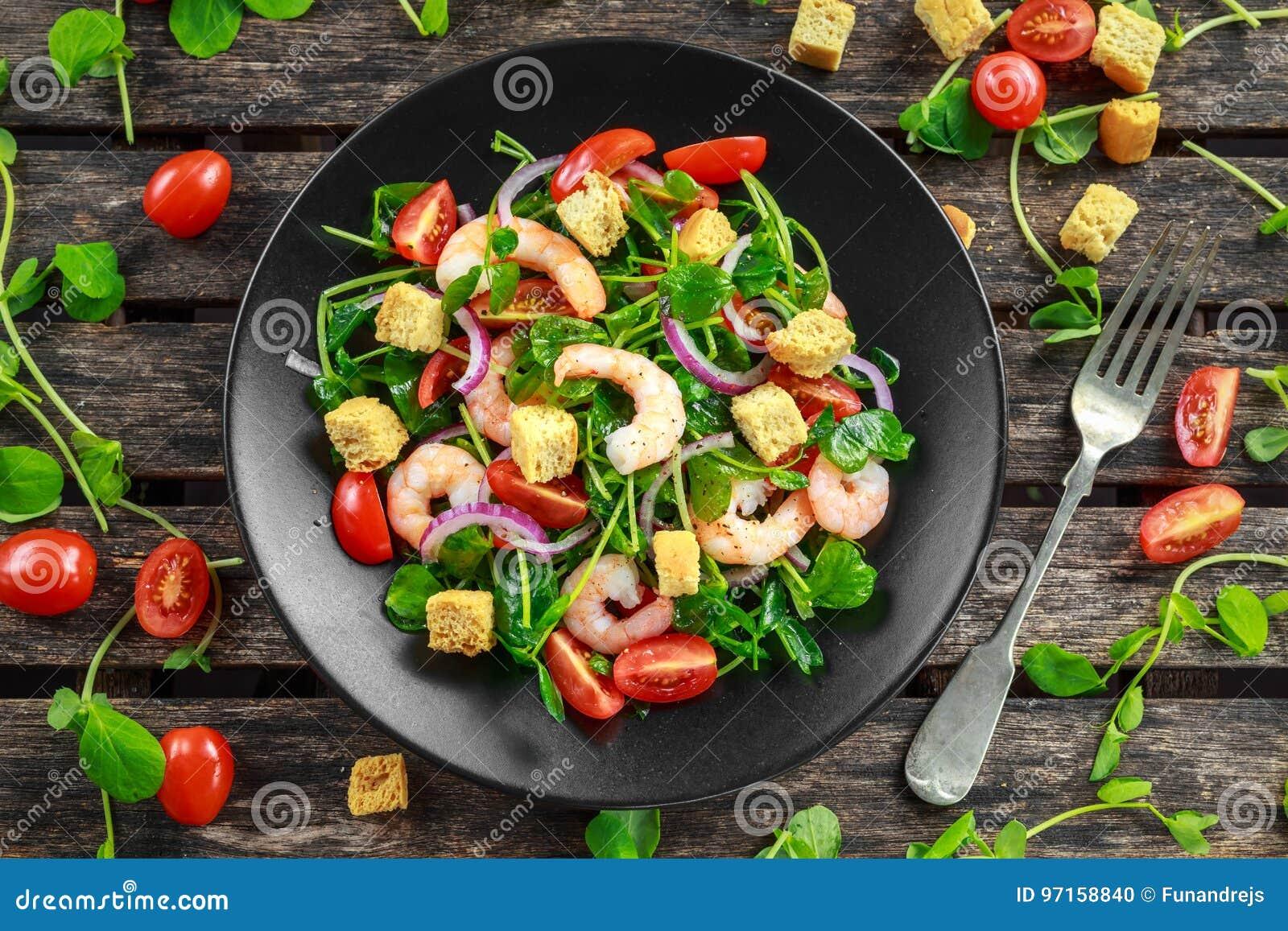 Свежий здоровый салат с томатами, красный лук креветок на черной плите Еда концепции здоровая