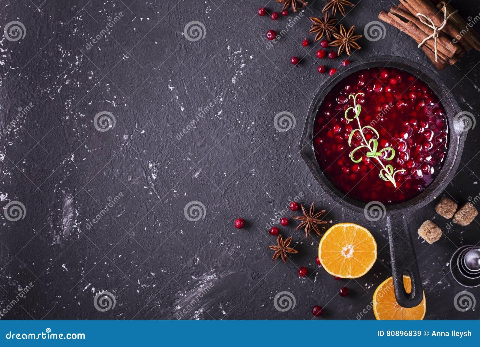 Свежий домодельный соус клюквы в лотке на темной деревянной предпосылке с разбрасывать зрелых ягод