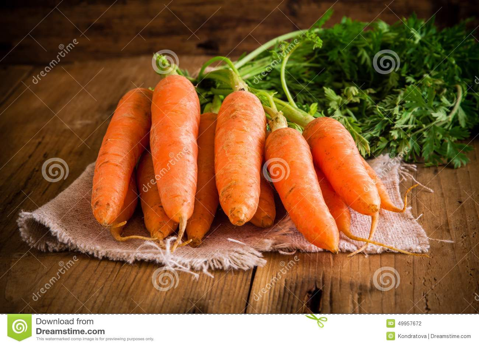 Свежий пук морковей на деревянной предпосылке