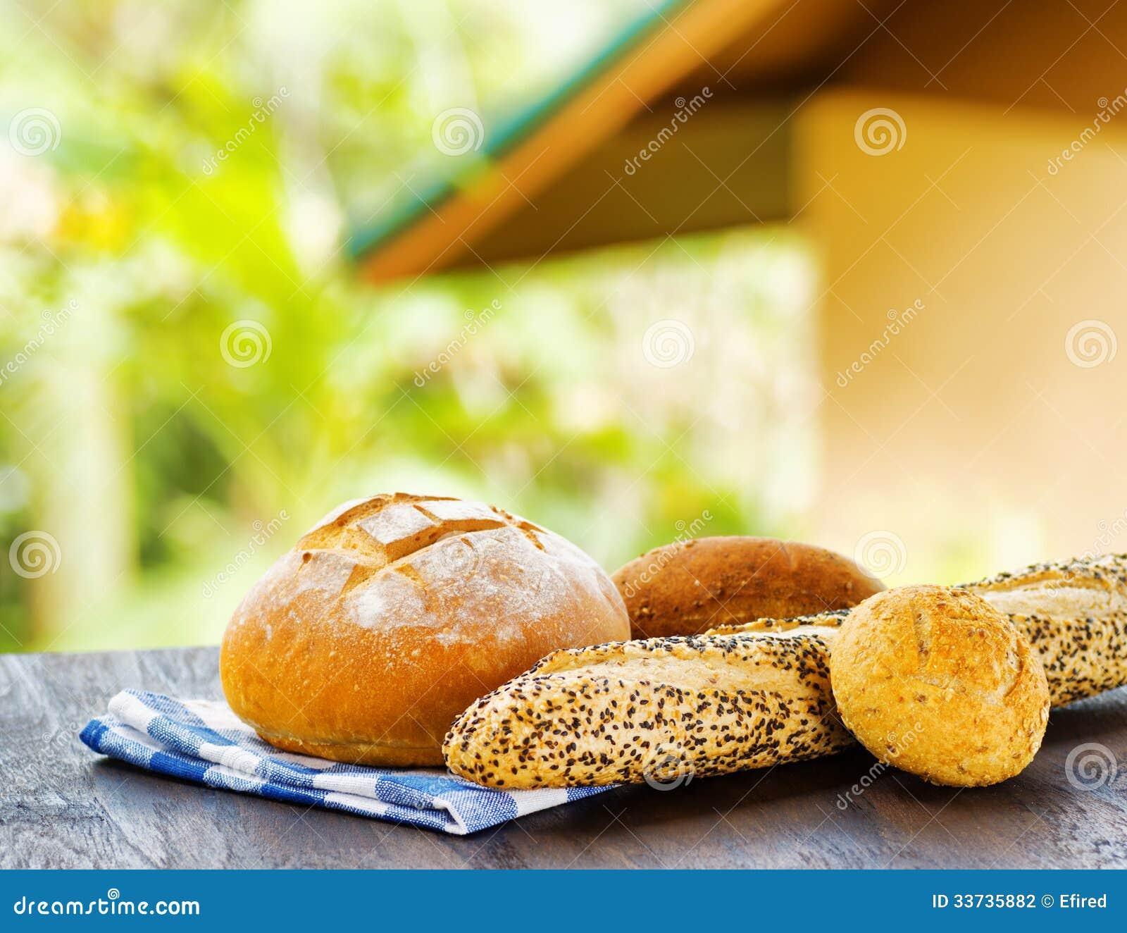 Свежий хлеб и checkered салфетка на деревянном столе на сельском backgr