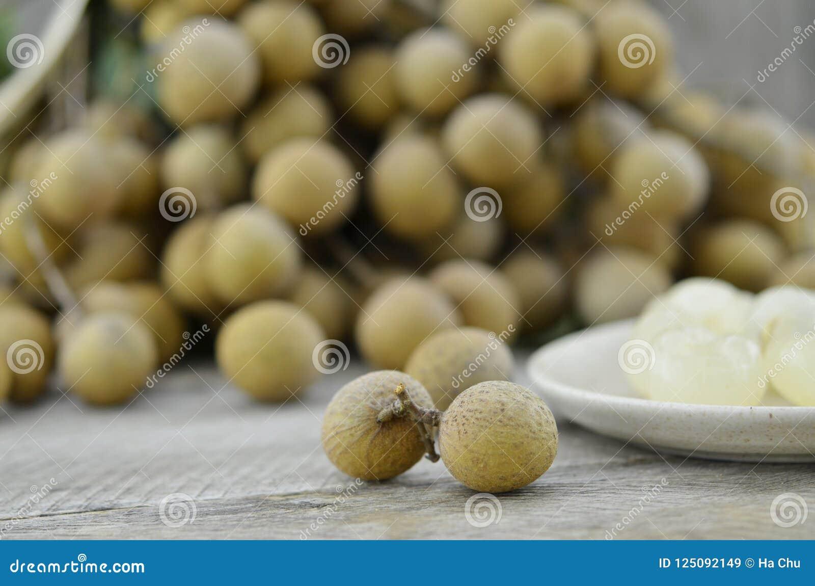 Свежий longan, извлекает семена в плите на деревянном столе