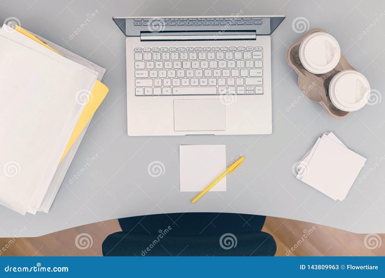 Сверху вниз части комнаты офиса включая таблицу, стул, ноутбук, бумажные стаканчики кофе, стикеры примечания и папки