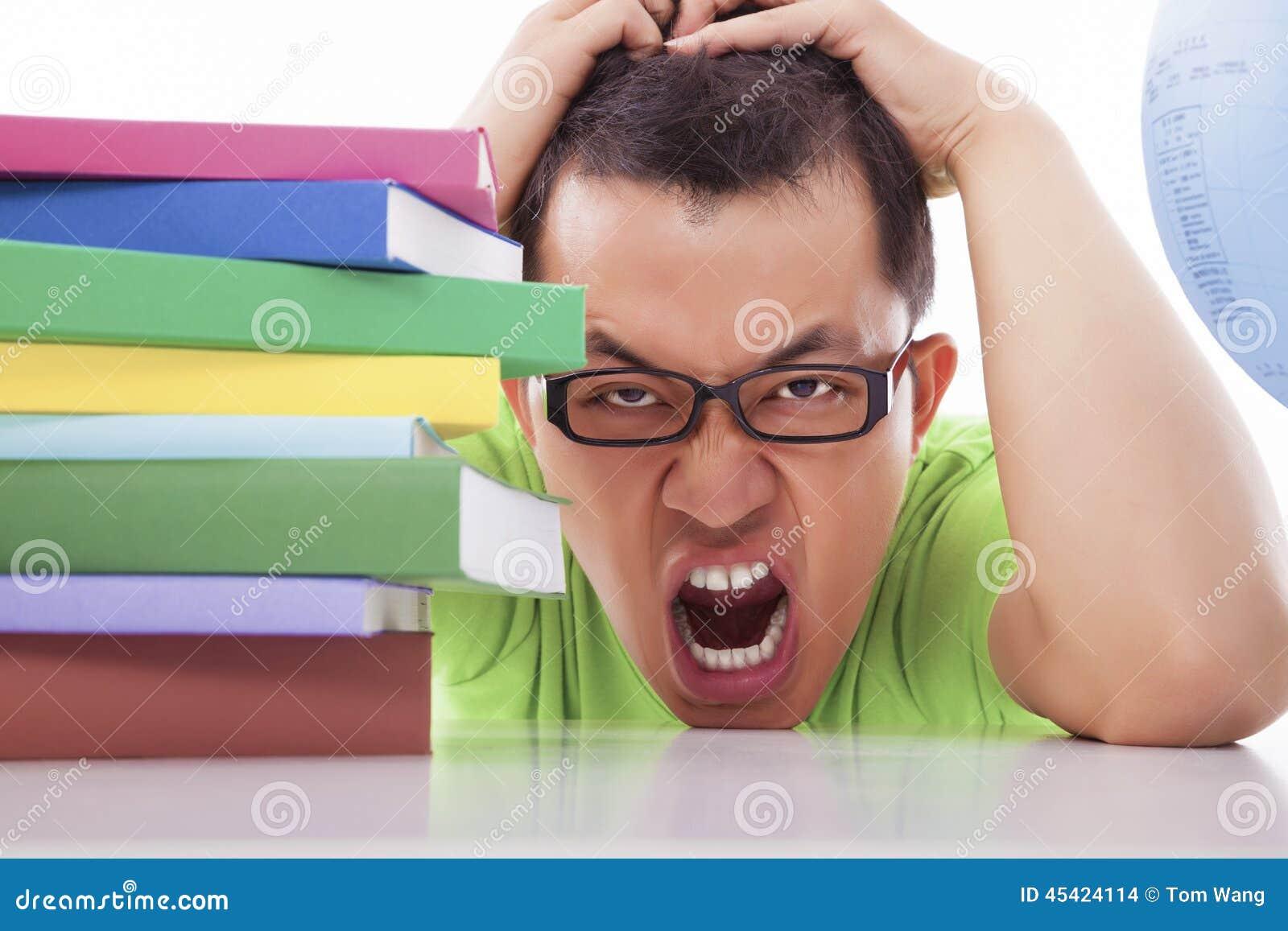 Сверлильный и утомленный молодой человек с много книг