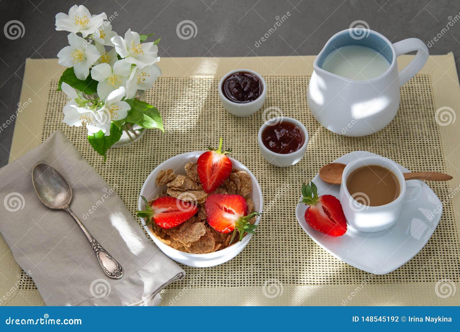 Светлый кофе завтрака с молоком и muesli, свежими клубниками, вареньем