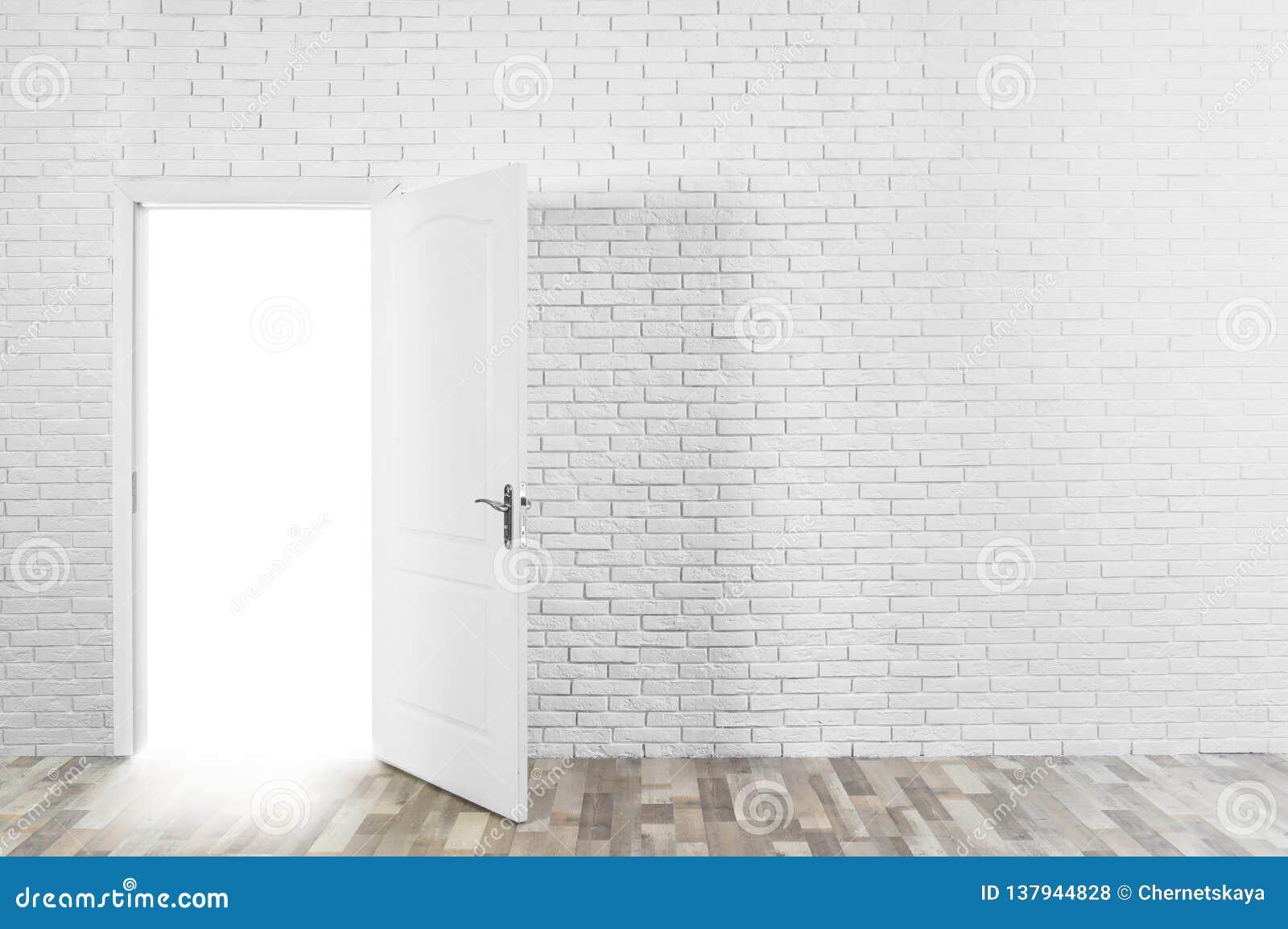 Свет приходя вне через раскрытую дверь в кирпичной стене