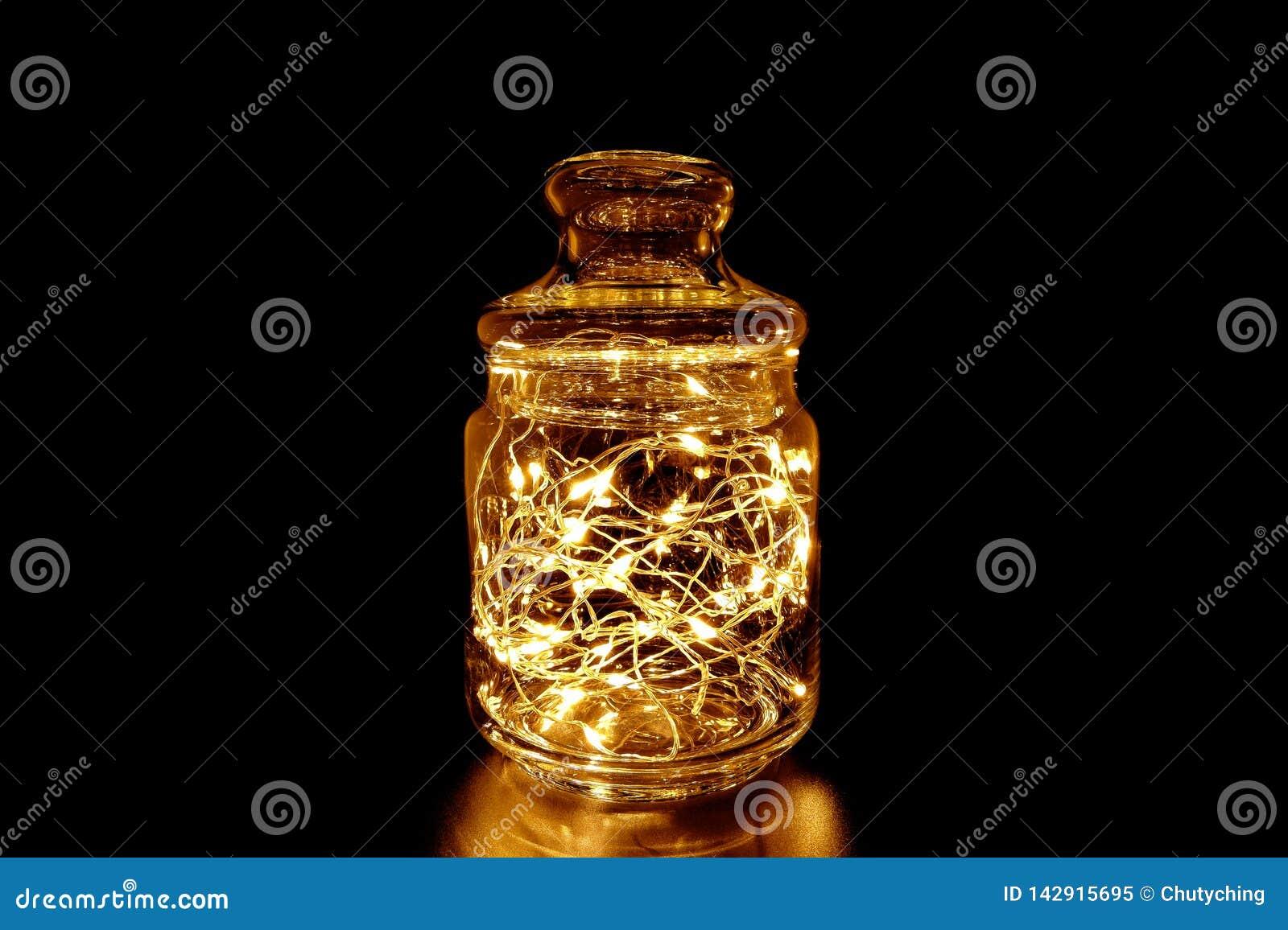 Свет феи в стеклянном опарнике на черной предпосылке