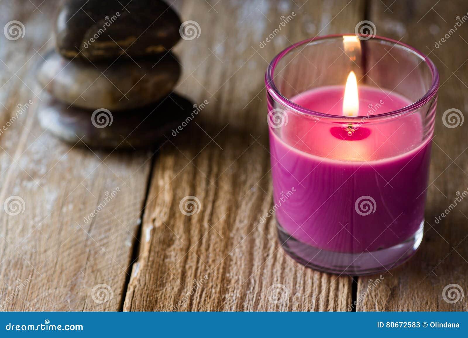 Свеча лаванды сирени и стог сбалансированного Дзэн облицовывают на заднем плане, на деревянной поверхности, copyspace для текста,