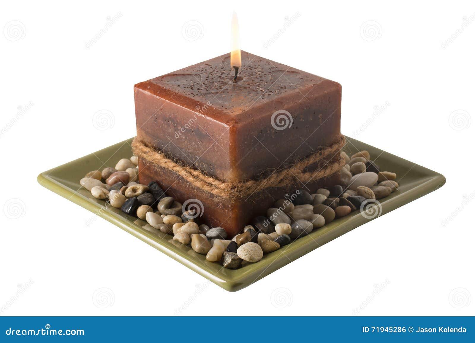 Свеча на плите при освещенные камни -