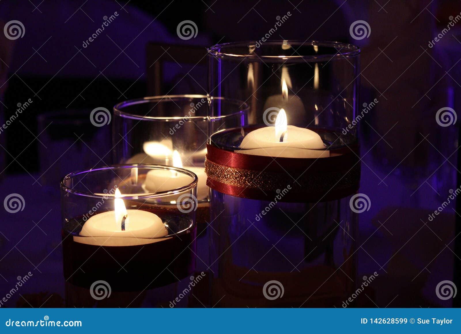Свечи Lit в стеклянных держателях с пурпурной предпосылкой