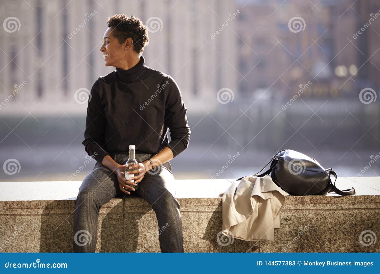 Свитер turtleneck молодой чернокожей женщины нося сидя в солнце на стене обваловки рекой Темза в Лондоне, подсвеченном
