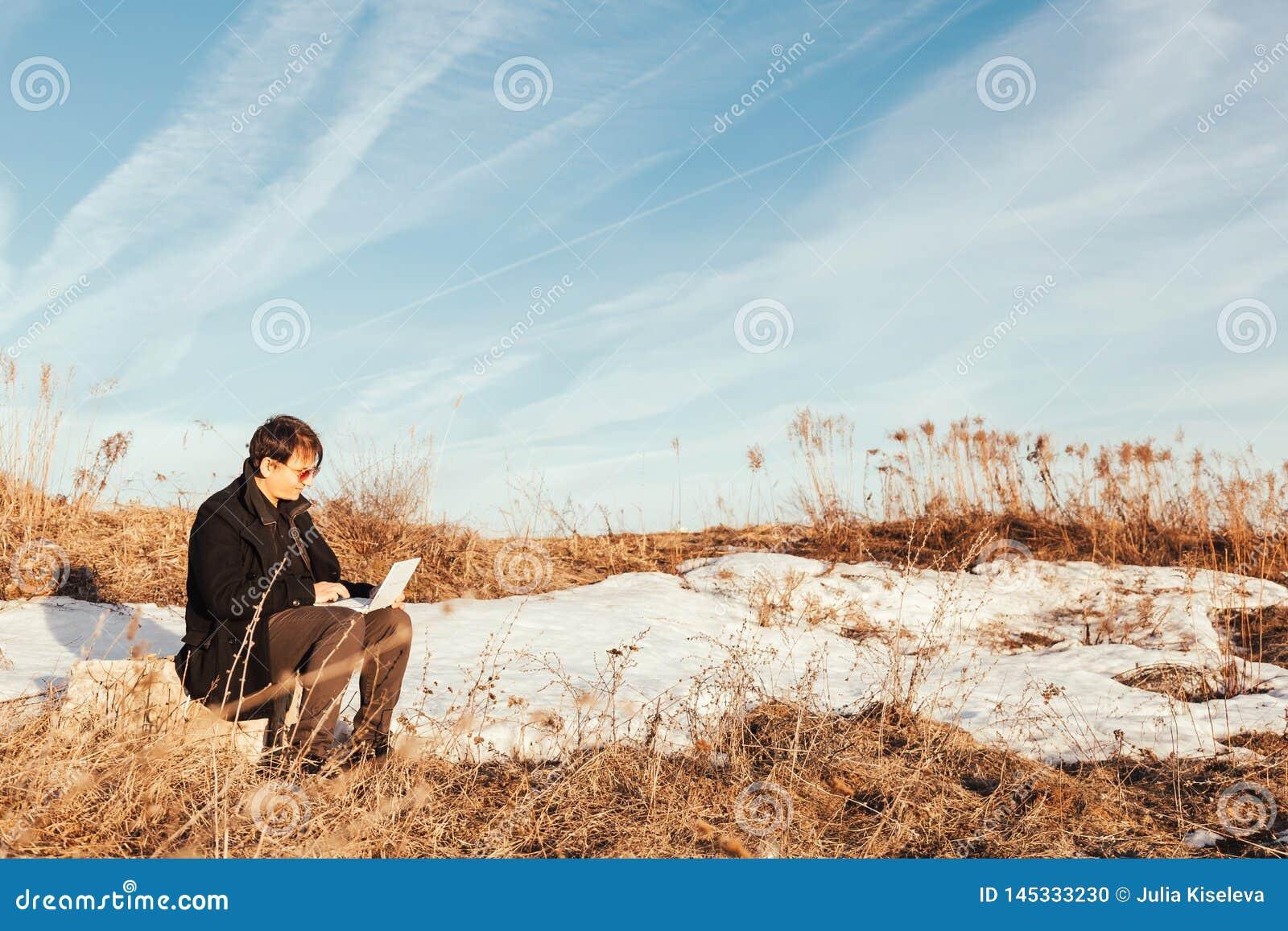 Свобода - человек используя ноутбук на открытом воздухе в парке с copyspace