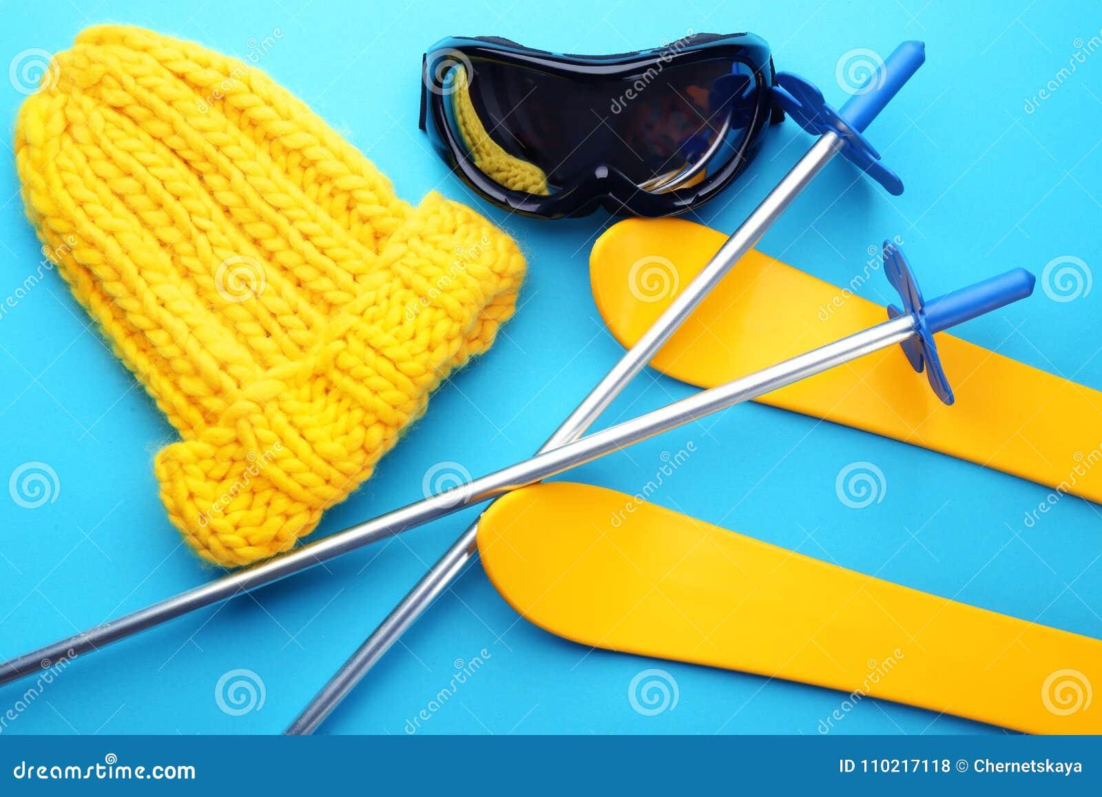 Связанная шляпа с обмундированием лыжи на предпосылке цвета