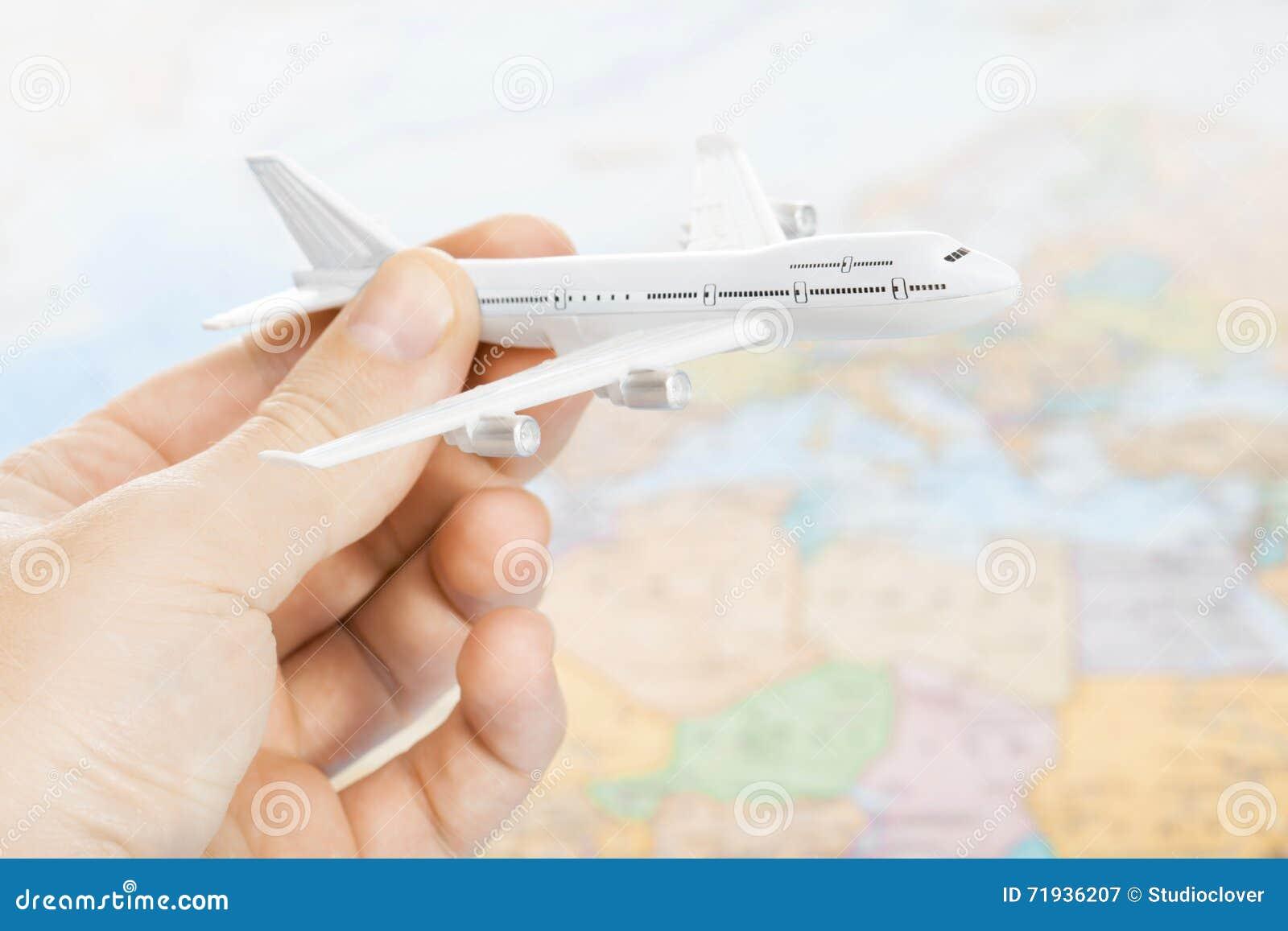 Связанные путешествовать, туризм, сообщения и все вещи - забавляйтесь самолет в руке с картой мира на предпосылке