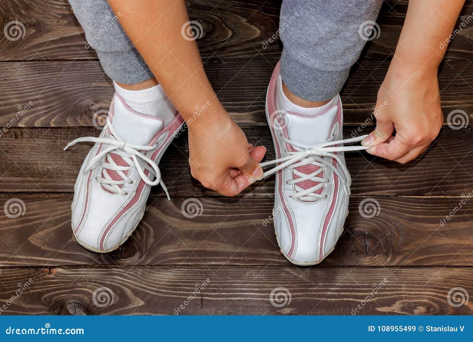 Связывать девушку шнурков ботинка сидя на деревянном поле Белая тапка