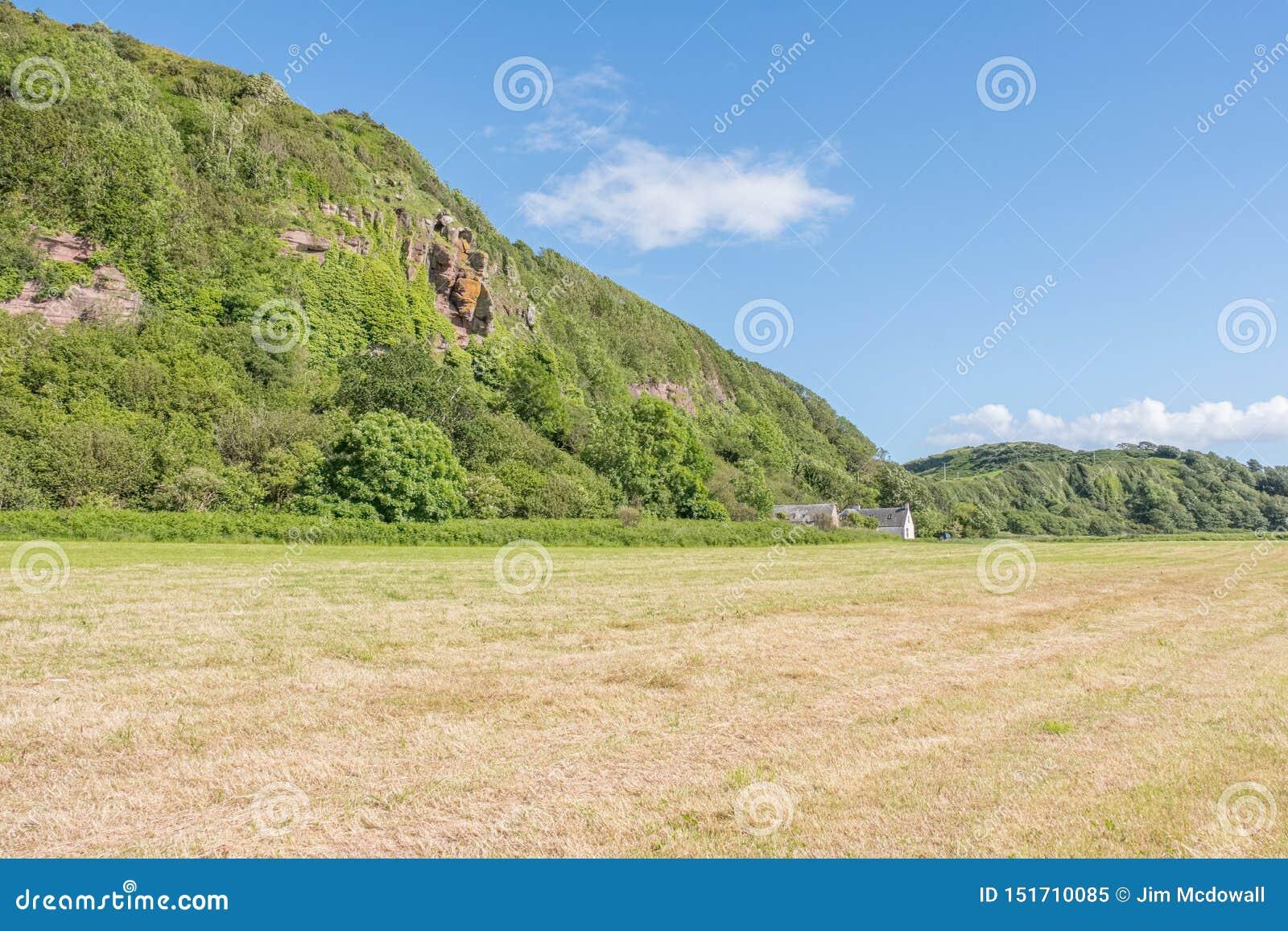 Святые пещеры или Hawking пещера Craig расположенные над земным Leval в Portencross на летнем солнцестоянии в Шотландии