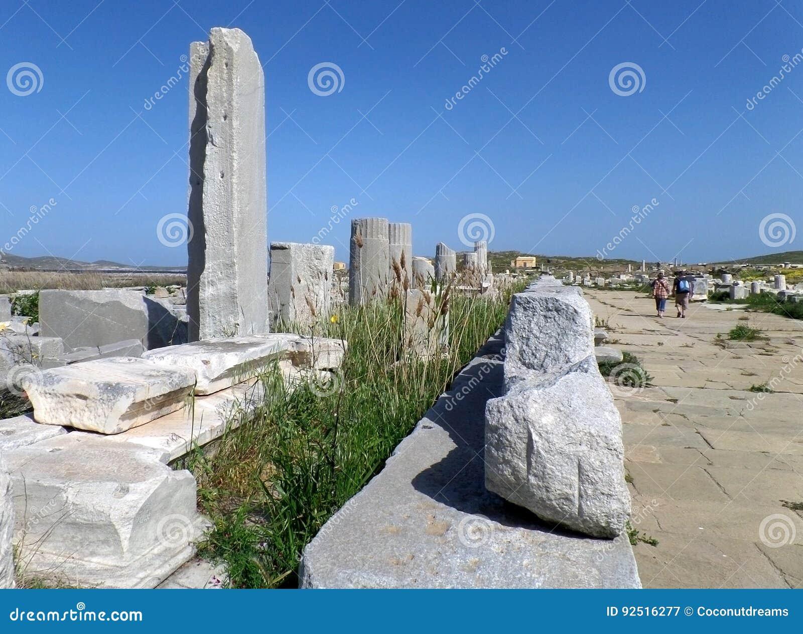Священный путь с старыми руинами в археологических раскопках Delos, месте всемирного наследия ЮНЕСКО на острове Delos