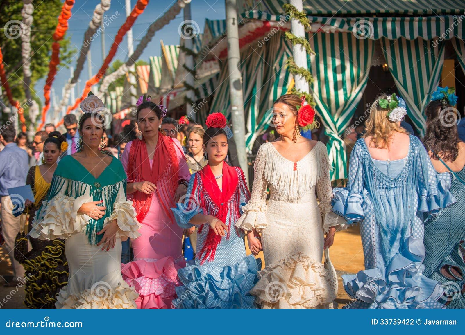 СЕВИЛЬЯ, ИСПАНИЯ - 25-ое апреля: Женщины в платье стиля фламенко на