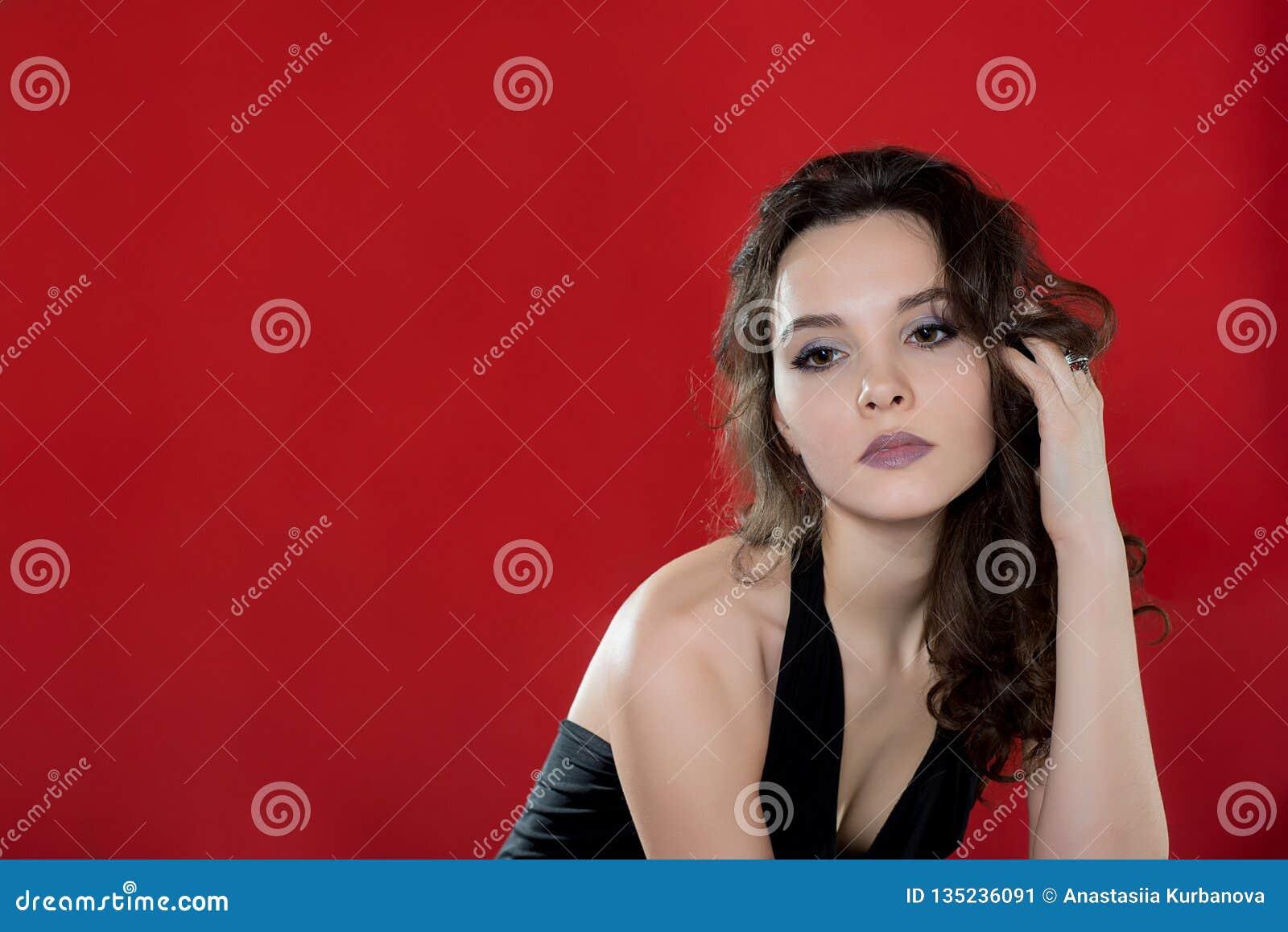 Сексуальная девушка брюнета на красной предпосылке