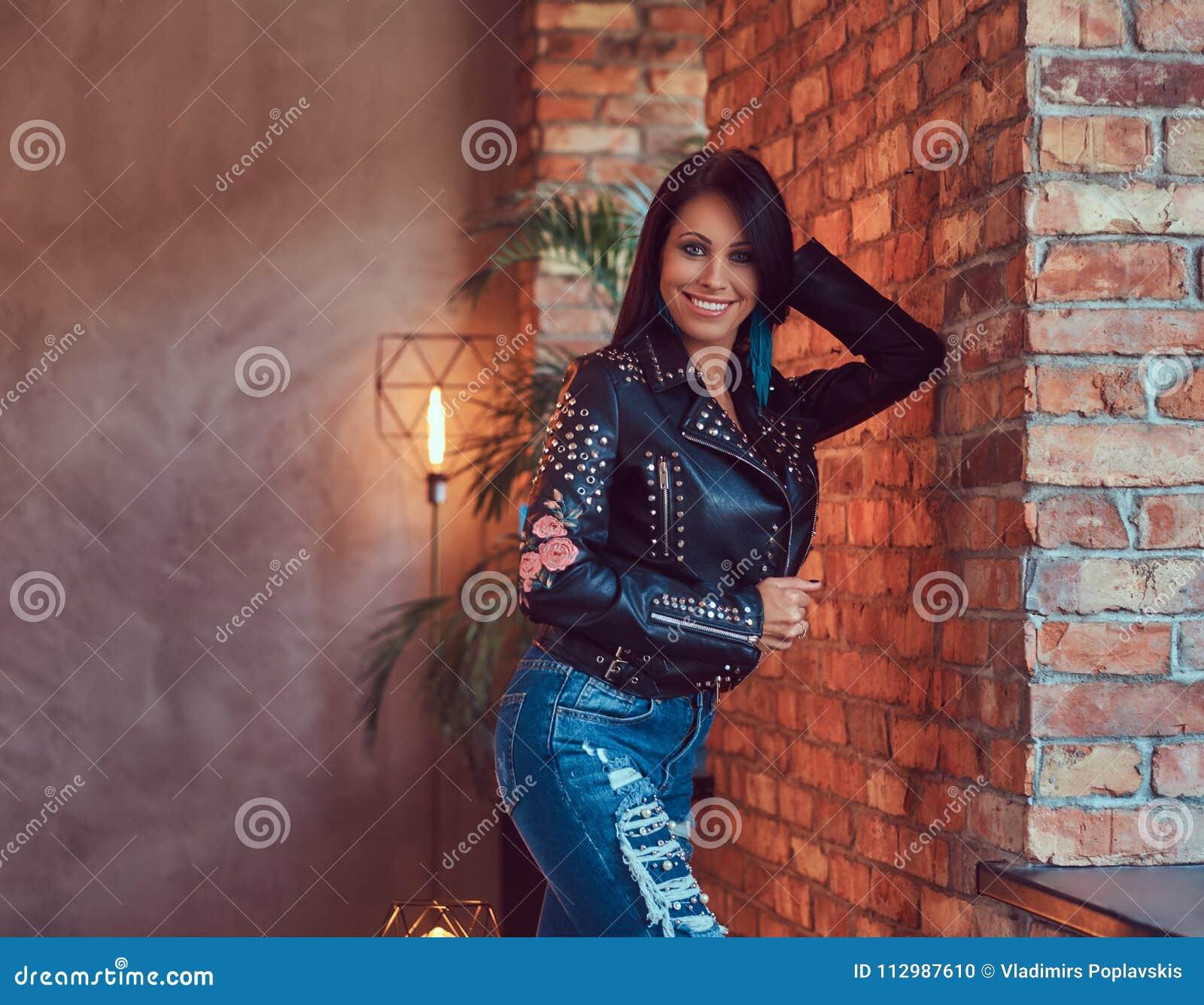 Сексуальное чувственное брюнет представляя в стильной кожаной куртке и джинсах полагаясь против кирпичной стены